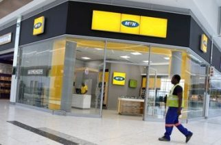 A worker walks past an outlet of South Africa's MTN Group in Johannesburg, South Africa, February 23, 2016. REUTERS/Siphiwe Sibeko/File Photo