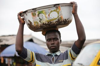 A man balances a bowl with a print of the old Nigerian naira banknote on his head at a local market in Agege district in Lagos, Nigeria on August 16, 2016. Since Nigeria's central bank announced it would abandon its currency's dollar peg, the naira has fallen 61 percent against the U.S. dollar. Photo by Akintunde Akinleye/Reuters