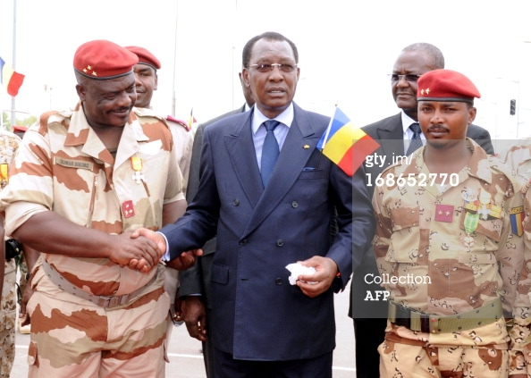 Chad's President Idriss Deby Itno (C) shakes hands with general of the Chadian contingent in Mali Oumar Bikimo (L) and second-in-command major and his son Mahamat Idriss Deby Itno (R) during a welcome ceremony, on May 13, 2013, in N'Djamena. Some 700 Chadian soldiers returned home to a heroes' welcome after a bloody campaign fighting Islamic insurgents in northern Mali. AFP PHOTO / STR (Photo credit should read STR/AFP/Getty Images)