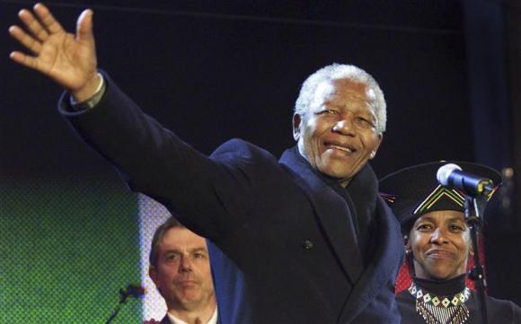 Nelson Mandela waves from the stage with British Prime Minister Tony Blair (L) and South African High Commissioner Cheryl Carolus at Trafalgar Square during the South African democracy concert, in this April 29, 2001 file photo. CREDIT: REUTERS/FILES