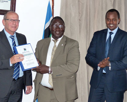 Michel Fest, the director of Gauff Ingenieure consultants (L), Uganda's Permanent Secretary in the Ministry of Works and Transport Okello Bwangamoi (C) and Guy Kalisa, the director-general of Rwanda Transport Development Agency, after signing the contract in Kampala yesterday. Gashegu Muramira.