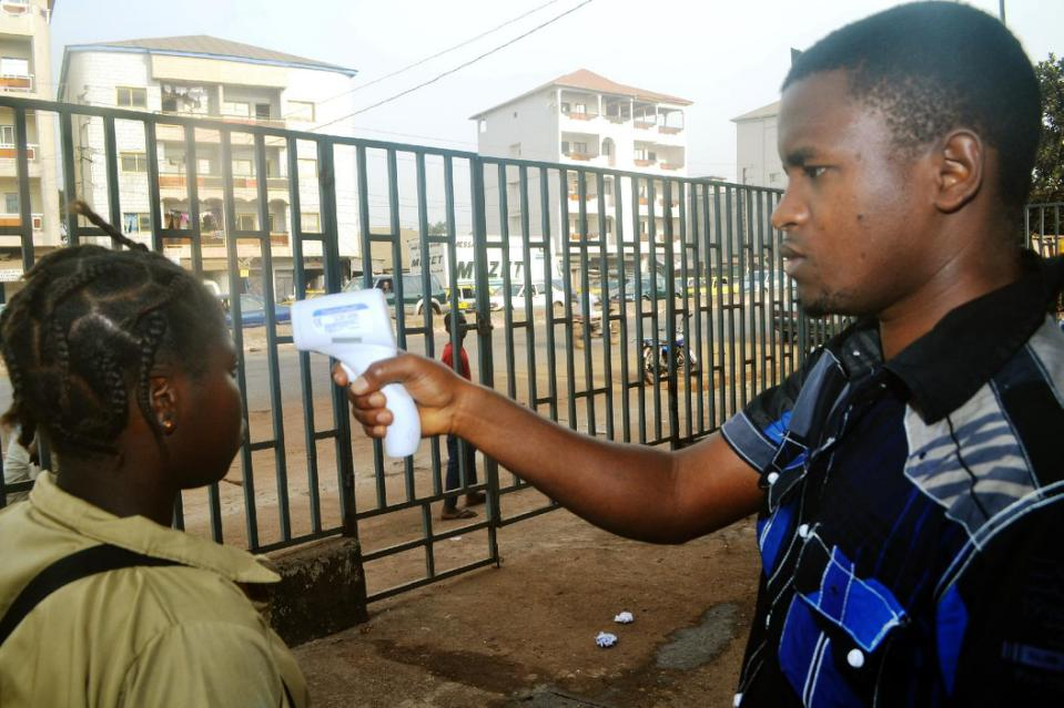 A Guinean student gets her temperature checked on January 19, 2015 outside the Oumou Diaby school in Conakry (AFP Photo/Cellou Binani)