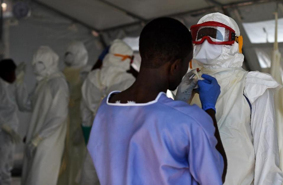 Health workers put on protective equipment at an Ebola treatment centre in Kenama, Sierra Leone, on November 15, 2014 (AFP Photo/Francisco Leong)