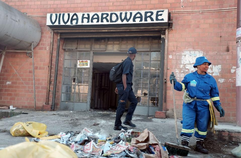 A worker from the eThekwini municipality cleans up after a xenophobic attack on a Somali businesses in Umlazi township, south of Durban, on April 10, 2015 (AFP Photo/Rajesh Jantilal)