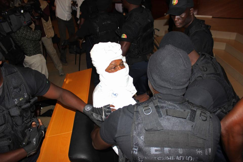 Security personnel surround former Chadian dictator Hissene Habre inside the court, in Dakar, Senegal, Monday, July 20, 2015,  The trial of former Chadian dictator Hissene Habre accused of overseeing the deaths of thousands had a chaotic beginning Monday as security forces ushered the ex-leader into and then out of the Senegal courtroom amid protests by his supporters. (AP Photo/Ibrahima Ndiaye)