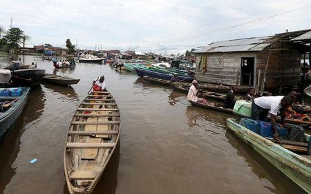 People ride in canoes and speedboats at Swali jetty near the banks of the Nun River on the outskirts of the Bayelsa state capital, Yenagoa, in Nigeria's delta region October 8, 2015.   REUTERS/Akintunde Akinleye