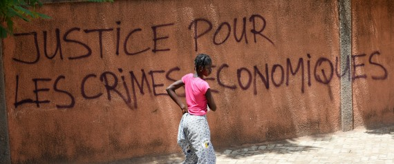 "A woman walks past a wall with graffiti reading ""Justice for the economic crimes"" in Ouagadougou on October 1, 2015. General Gilbert Diendere, the leader of Burkina Faso's short-lived coup, was in police custody on October 1, a security source told AFP.  AFP PHOTO / SIA KAMBOU        (Photo credit should read SIA KAMBOU/AFP/Getty Images)"