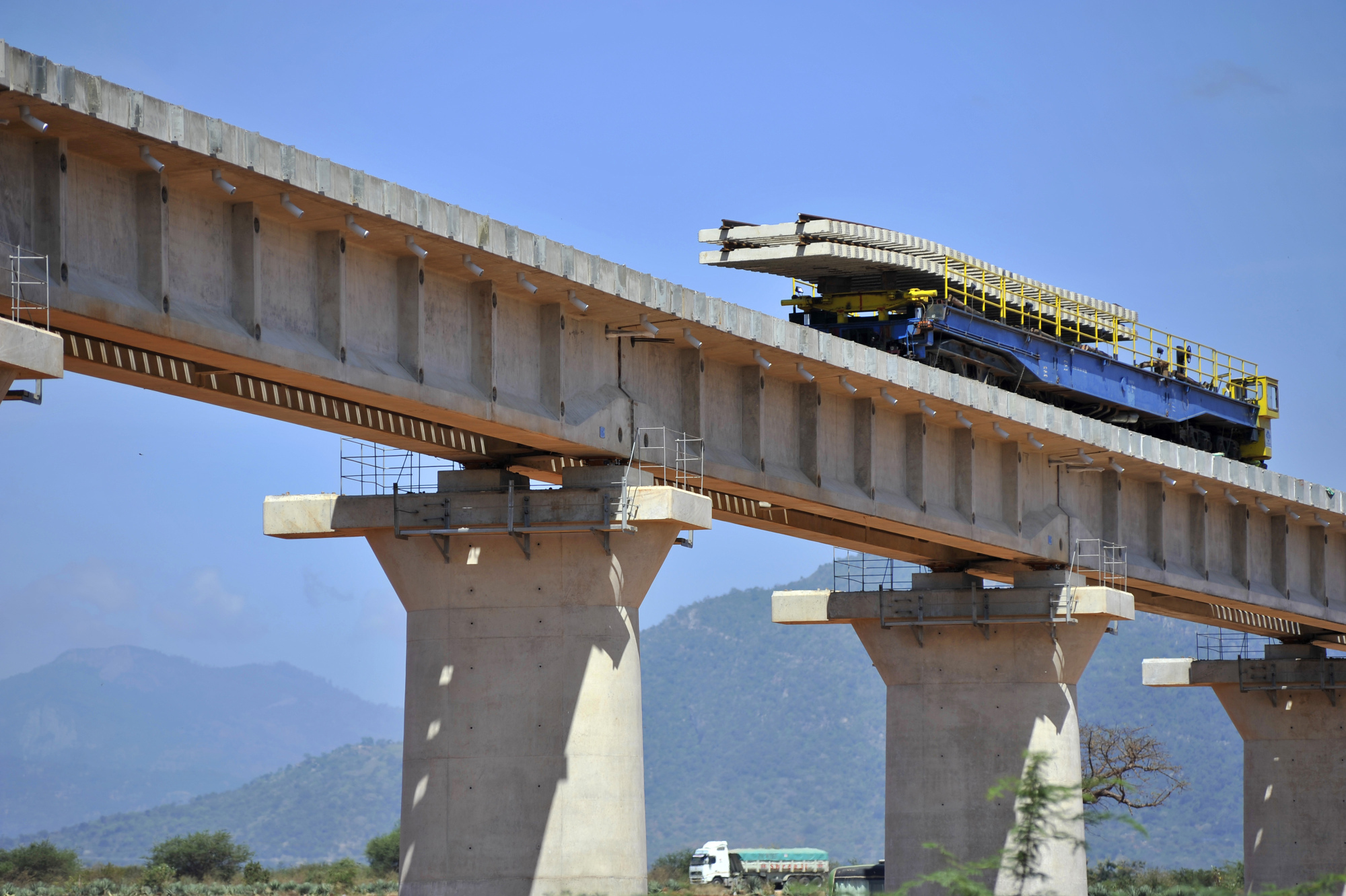 A rail wagon carries sections of railway sleepers and tracks towards the bridge end during the construction of a superbridge which will form part of the new Mombasa-Nairobi Standard Gauge Railway (SGR) line, in Voi, Kenya, on Wednesday, March 16, 2016.  By providing an alternative to roads, the 1,100-kilometer (684-mile) Chinese-financed railway will slash the time and cost of transporting people and goods between East Africa's landlocked nations. Photographer: Riccardo Gangale/Bloomberg