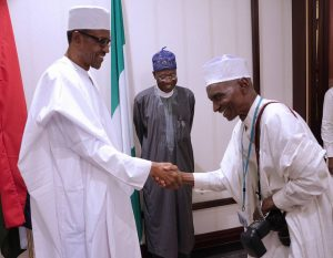 L-R; President Muhammadu Buhari in a handshake with the Oldest Photojournalist of Triumph Newspapers in the State House, Alhaji Ladan Abubakar. With them is the Minister of Information, Alhaji Lai Mohammed , SSA Shehu Garba. MAY 30, 2016