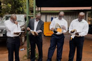 Men in Kampala look over their paperwork to go to Iraq for Saracen International security: visas, contracts, yellow fever vaccination documents, and flight tickets.