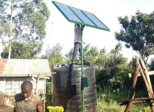 Rwandan farmers erect a solar-powered pump that will be used to irrigate their fields. TRF/Karuma Njoroge
