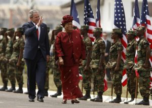 "Sirleaf inspects an honor guard in Monrovia with a visiting President George W. Bush in 2008. ""There is not another woman that you can huddle with and plan your strategies with,"" she says of many gatherings with world leaders. ""You're not going to go out and have beer together."" (Jim Young/Reuters)"