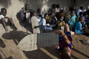 Boys recite Quranic verses handwritten on pieces of wood during a religious class in front of the Grand Mosque of Djenne, Mali September 1, 2012. REUTERS/Joe Penney