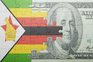 A puzzle with the national flag of Zimbabwe and a US dollar banknote. (Image: Shutterstock)