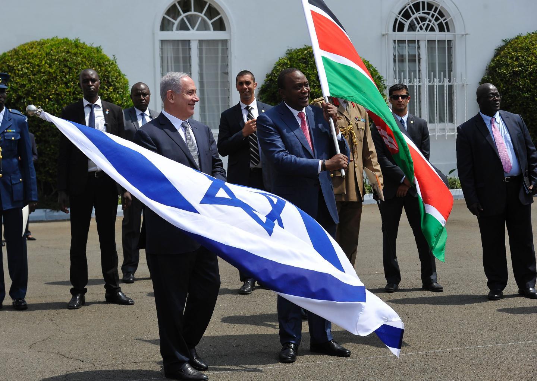 Israeli Prime Minister Benjamin Netanyahu (L) and Kenyan President Uhuru Kenyatta (R) wave their national flags after a press conference in Nairobi, Kenya, July 5. Netanyahu's visit caused gridlock on Nairobi's roads. SIMON MAINA/AFP/GETTY IMAGES