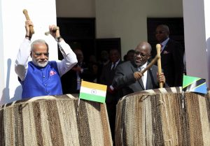 Indian Prime Minister Narendra Modi, left, and his host Tanzanian President John Pombe Magufuli, right, beat drums at the entrance of State House during an official welcome ceremony for Modi in Dar es Salaam Tanzania Sunday July 10, 2016. Modi is on his third leg of his Africa tour. (Khalfan Said/Associated Press)