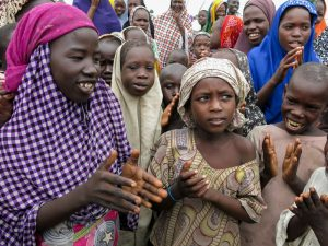 They're not in class, so to while away the time Maimuna Bundi, second from right, sings with her friends at Muna camp. Ofeibea Quist Arcton/NPR