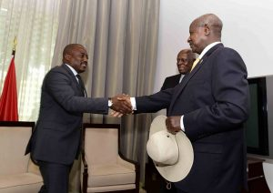 Museveni shakes hands with Kabila (L) in Angola during the ICGLR Summit in June