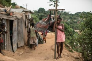 A girl stands beside a laundry line in a poor neighborhood overlooking Cabinda, a heavily guarded territory that accounts for half of Angola's oil output. (Nichole Sobecki/For The Washington Post)