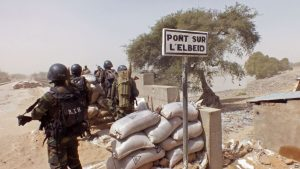 FILE - Cameroonian soldiers guard against Boko Haram militants on Elbeid bridge near the village of Fotokol, on the border with Nigeria's Borno state. Militant attacks have fed demand for private security firms, now the focus of a government clampdown.