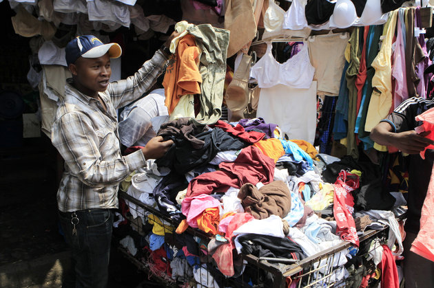 NOOR KHAMIS / REUTERS A vendor sells secondhand cloths at a stall in the busy Gikomba market in Nairobi, Kenya, Sept. 18, 2014. Shaded by ragged squares of canvas, amid choking dust and the noise of hawkers, shoppers can turn up Tommy Hilfiger jeans or a Burberry jacket for a fraction of the price in London's Regent Street or New York's Fifth Avenue. This ar