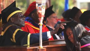 Zimbabwean President Robert Mugabe, left, places a cap on a student at the University of Zimbabwe, during graduation ceremony in Harare, Thursday, Sept, 29, 2016. (AP Photo/Tsvangirayi Mukwazhi)  (The Associated Press)