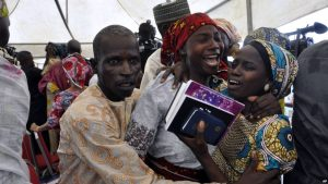 One of the freed Chibok girls celebrates with family members during a church service in Abuja, Nigeria, Oct. 16, 2016. Twenty-one girls were released Thursday and flown to Abuja, Nigeria's capital, but it's taken days for relatives to arrive.s