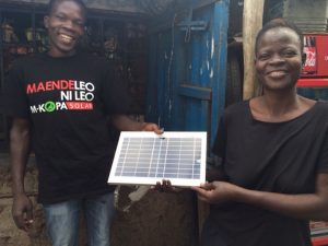 Consonlata Andhiambo Odero, who lives in western Kenya and is seen here with an M-KOPA sales rep, is all smiles as she shows off new solar panel that is powering solar-powered lamps so so her kids can read at night. M-KOPA's pay-as-you-go household solar systems have been a huge hit all across East Africa.