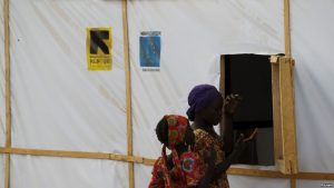 FILE - A woman and a girl are seen outside makeshift accommodations at camp for internally displaced people in Maiduguri, Nigeria, March 8, 2016.