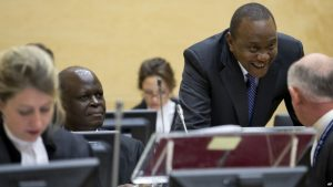 FILE - Kenya President Uhuru Kenyatta, second right, talks to his defense team when appearing before the International Criminal Court (ICC) in The Hague, Netherlands, Oct. 8, 2014.