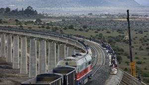 In this photo taken Wednesday, Nov. 23, 2016, a train returns from transporting ballast used in the construction of the Nairobi-Mombasa railway, and passes over an existing bridge that goes across a corner of Nairobi National Park in Nairobi, Kenya. A controversial Chinese-built railway project involving an even larger 6km bridge that would go all the way over the beloved protected area in Kenya's capital has divided conservationists in this East African country. (Ben Curtis/Associated Press)