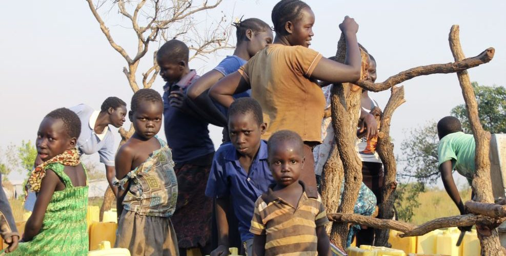 A group of children and adults gather around a bore-hole in the Bidi bidi refugee settlement in Bidi bidi, Uganda, Dec. 10, 2016.