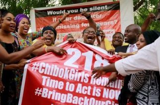 """Members of the #BringBackOurGirls (#BBOG) campaign react on the presentation of a banner which shows """"218"""", instead of the previous """"219"""", referring to kidnapped Chibok school girls, during a sit-out in Abuja, Nigeria May 18, 2016, after receiving news that a Nigerian teenager kidnapped by Boko Haram from her school in Chibok more than two years ago has been rescued. REUTERS/Afolabi Sotunde"""