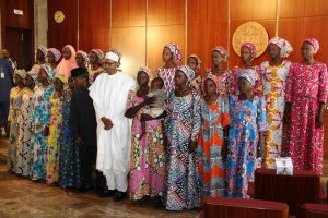 Nigerian President Muhammadu Buhari (C) poses on October 19, 2016 with the 21 Chibok girls who were released by Boko Haram last week, at the State House in Abuja, Nigeria. Speaking at the presidential villa in Nigeria's capital of Abuja, Buhari addressed the girls and their families saying 'we shall redouble efforts to ensure that we fulfil our pledge of bringing the remaining girls back home'. / AFP / Philip OJISUA
