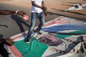 A supporter of Gambia's President-elect Adama Barrow walks over a poster of the incumbent Yahya Jammeh, Serekunda, December 2. Jammeh's decision to reject the election result has left observers fearing unrest, and potentially violence, in Gambia. MARCO LONGARI/AFP/GETTY