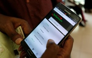 An employee assists a customer to set-up M-Pesa money transfer service on his handset inside a mobile phone care center operated by Kenyan's telecom operator Safaricom, in Kenya's capital Nairobi on May 11. Mobile money apps like M-Pesa have revolutionized personal finance in Kenya. THOMAS MUKOYA/REUTERS