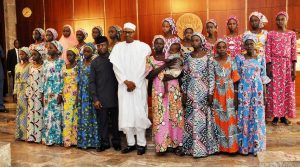 Nigerian President Muhammadu Buhari (C) poses at State House in Abuja on October 19, 2016 with the 21 Chibok girls who were released by Boko Haram the previous week (AFP Photo/Philip OJISUA)