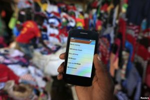 FILE - A man holds up his mobile phone showing an M-Pesa mobile money transaction page at an open-air market in Kibera in Kenya's capital, Nairobi, Dec. 31, 2014.