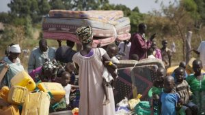 FILE - Refugees who fled violence in South Sudan await transportation from a transit center in the town of Koboko, Uganda, Jan. 6 2014.