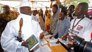 Yahya Jammeh holds a copy of the Quran while speaking to a poll worker at a voting station [Thierry Gouegnon/Reuters]