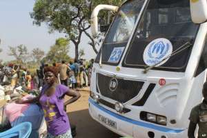 FILE - A women from South Sudan stands in front of a UNHCR passenger bus next to a refugee registration site near Bibi Bidi, Uganda, Dec. 11, 2016.