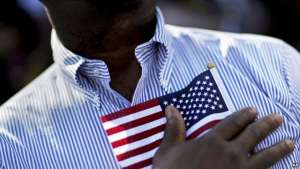 A candidate for citizenship holds the American flag against his chest during the playing of the national anthem at the start of a naturalization ceremony for 755 new United States citizens at Turner Field, home of the Atlanta Braves baseball team in Atlanta, Friday, Sept. 16, 2016. The ceremony, in honor of Constitution Day and Citizenship Day, was the largest in Georgia this year and the 755 citizens sworn in marks the number of home runs hit by former Braves player Hank Aaron. (AP Photo/David Goldman)