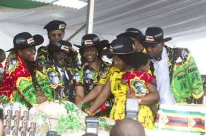 Zimbabwean President Robert Mugabe and his wife Grace  are joined by the his family as they cut the cake during his 93rd Birthday celebrations in  Matopos on the outskirts of Bulawayo, Saturday, February, 25, 2017.Mugabe is celebrating his 93rd birthday amid granite hills were spirits are said  to dwell, defying calls to resign after nearly four decades in power with a  celebration in in a region for opposing a  leader who says  he will run  again in 2018 elections(AP Photo/Tsvangirayi Mukwazhi)