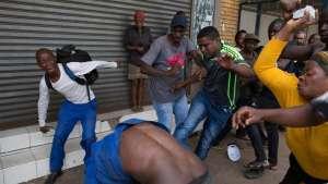 A Nigerian migrant comes under attack outside a church in Pretoria on Saturday [James Oatway/Reuters]