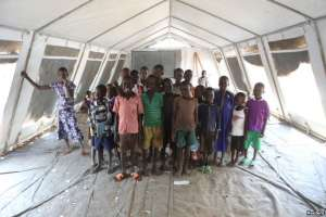 FILE - Children who fled fighting in South Sudan pose for a photograph inside a tented classroom at Bidi Bidi refugee's resettlement camp near the border with South Sudan, in northern Uganda Dec. 7, 2016.