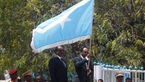 Somalia's newly elected President Mohamed Abdullahi Mohamed, right, flanked by outgoing president Hassan Sheikh Mohamud carries their national flag during the hand-over ceremony at the Presidential palace in Somalia's capital Mogadishu, Feb. 16, 2017.