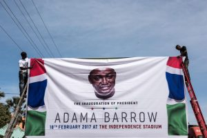 Men hang a banner for the inauguration ceremony of Gambian President Adama Barrow prior to his return on January 26 in Banjul, Gambia. The EU will release aid money to Gambia which was frozen under the country's previous leader Yahya Jammeh.