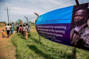 People walk near a banner of former child soldier-turned-warlord Dominic Ongwen before the screening of the start of his ICC (International Criminal Court) trial in Lukodi, Uganda on December 6, 2016 (AFP Photo/ISAAC KASAMANI)
