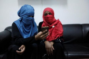 Eritrean migrant Minya Mesmer (R) looks at a smartphone with her daughter at a military building in Misrata, Libya, November 6, 2016.