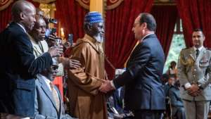 French President Francois Hollande (centre right) shakes the hand of one of the veterans